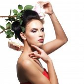 Portrait of beautiful young woman with flowers in hair touching her face - isolated on white
