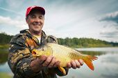 Happy smiling fisherman holding his trophy carp (Cyprinus carpio) with pond on the background. Focus