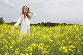 Beautiful and sensuality young adult brunette woman in a yellow flowers field