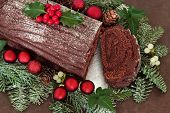 Chocolate yule log cake with red bauble decorations, holly, ivy, mistletoe and snow covered fir over