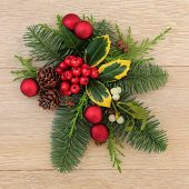 Christmas floral decoration with red baubles, holly, ivy mistletoe and pine cones over oak wood back