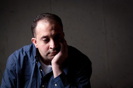 pic of saddening  - A middle aged man with a contemplative look on his face - JPG