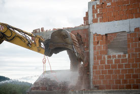 picture of backhoe  - View of the hydraulic arm and bucket of a large heavy duty backhoe demolishing a brick house breaking down the exterior wall for removal - JPG