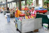 BANGKOK, THAILAND - MARCH 22, 2009: Thai flower vendor sells  Buddhist flowers on the street.
