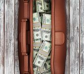 Suitcase Full Of Dollars On A Wooden Background. View From Above