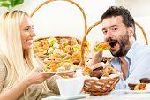 Woman feeds man a sandwhch
