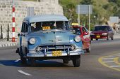 People ride in a vintage taxi car in Havana, Cuba.