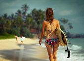 Young lady walking with surf board on sandy tropical beach