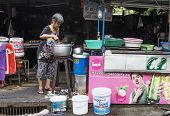 BANGKOK, THAILAND - DECEMBER 25, 2014: Street Photography of Street market in China town. Elderly woman cooking soup in a large vat.