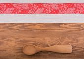 An old red and white patterned kitchen towel on dark wood background, with a wooden spoon and copy space in the center
