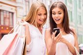 pic of young adult  - Two surprised young women holding shopping bags and looking at mobile phone together while standing outdoors - JPG
