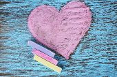 Heart drawn of chalks on wooden background close-up