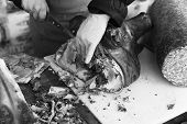 stock photo of spit-roast  - Black and White image of person and Roast Pork at Street Market - JPG