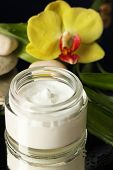 Face cream with orchid flower on dark background