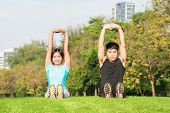Young Couple Stretching Before Exercise Together In Park