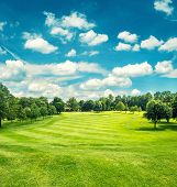 Golf Field And Blue Cloudy Sky. Beautiful Landscape With Green Grass