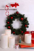 Christmas decoration with wreath and candles on shelf on white wall background