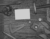 black and white image of a vintage jeweler tools and diamonds over wooden bench, space for text on a blank businesscard