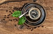 Cup Of Black Coffee With Beans And Leaves On Wooden Table