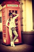 Beautiful young woman walking in the city. Europe, England. Vacation, tourist trip. Vintage style.