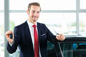 Seller or car salesman in car dealership with key presenting his new and used cars in the showroom