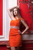 Woman In Orange Dress On Red Retro Wall