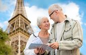 family, age, tourism, travel and people concept - senior couple with map and city guide over eiffel tower and blue sky background