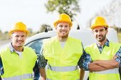 business, building, teamwork and people concept - group of smiling builders in hardhats on car background outdoors