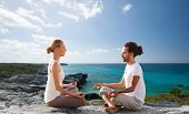 fitness, sport, people, yoga and lifestyle concept - happy couple meditating in lotus pose on summer beach