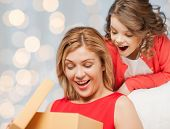 people, holidays, christmas and family concept - happy mother and daughter opening gift box over holiday lights background