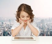 people, technology, education and children concept - happy smiling girl with tablet pc computer over city background