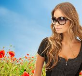 people, fashion, elegance and style concept - beautiful young woman in shades over blue sky and poppy field background