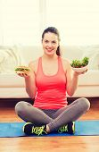 fitness, home and diet concept - smiling teenage girl with green salad and hamburger at home