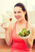 healt, dieting, home and happiness concept - smiling sporty teenage girl with green salad at home
