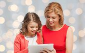 family, technology, people and christmas holidays concept - happy mother and daughter with tablet pc computer over lights background