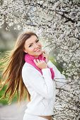 Beautiful girl in spring flowered Park.