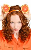 Close-up portrait of a young woman with oranges.