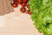 Lettuce, Tomatoes And Rye Bread On Wooden Background