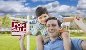 Mixed Race Father and Son Celebrating with a Piggyback in Front Their House and For Sale Real Estate Sign.