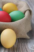 Painted Easter Eggs In Basket On Wood Table