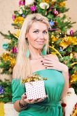 Pretty woman with present near Christmas tree