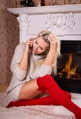 Young pretty woman talks on phone near fireplace