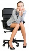 Businesswoman on office chair with head reclined upon her hands