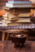 Candle On Wooden Table With Books In Background