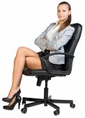Businesswoman in office chair with straight back and crossed legs