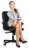 Businesswoman on office chair, with hand propping her cheek