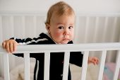 sad kid standing in crib
