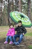 Spring In The Woods On A Stump Sits A Boy With A Girl Under An Umbrella.
