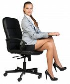 Businesswoman on office chair, holding clipboard