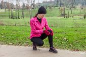 Young athlete woman hurting from a knee injury on a cold winter day in the track of an urban park.